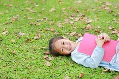 Ευτυχής λίγο κορίτσι παιδιών με το βιβλίο που βρίσκεται στην πράσινη χλόη με τα ξηρά φύλλα στο θερινό κήπο στοκ φωτογραφίες με δικαίωμα ελεύθερης χρήσης