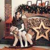 Ευτυχής λίγο κορίτσι brunette με τη μακρυμάλλη συνεδρίαση σε ένα άλογο παιχνιδιών Στοκ Φωτογραφία