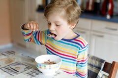 Ευτυχής λίγο ξανθό αγόρι παιδιών που τρώει τα δημητριακά για το πρόγευμα ή το μεσημεριανό γεύμα Υγιής κατανάλωση για τα παιδιά Στοκ Φωτογραφίες
