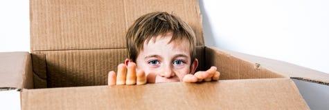 Ευτυχής λίγο παιδί που κρύβει σε ένα κουτί από χαρτόνι, peekaboo παιχνιδιού στοκ εικόνες