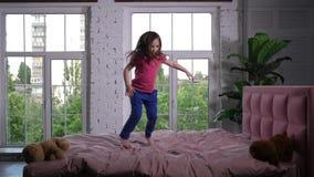 Ευτυχής λίγο παιδί που πηδά στο άνετο κρεβάτι στην κρεβατοκάμαρα απόθεμα βίντεο