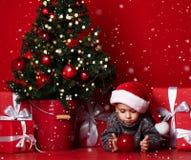 Ευτυχής λίγο χαμογελώντας αγόρι με τη σφαίρα Χριστουγέννων στοκ φωτογραφία