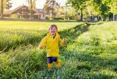 Ευτυχής λίγο χαμογελώντας αγόρι στο φωτεινό κίτρινο αδιάβροχο και τις λαστιχένιες μπότες που τρέχουν μέσω του τομέα με την πράσιν στοκ εικόνες