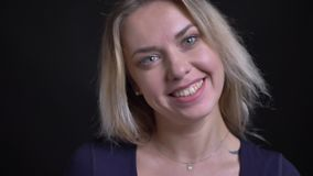 Ευτυχής μέσης ηλικίας ξανθή επιχειρηματίας στα μπλε ρολόγια μπλουζών με το flirty χαμόγελο στη κάμερα στο μαύρο υπόβαθρο απόθεμα βίντεο