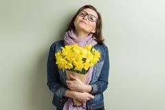 Ευτυχής μέση ηλικίας γυναίκα με την ανθοδέσμη των κίτρινων λουλουδιών, πράσινο υπόβαθρο τοίχων στοκ φωτογραφίες