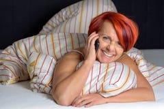 Ευτυχής μέση ηλικίας γυναίκα που κάνει ένα τηλεφώνημα Στοκ φωτογραφία με δικαίωμα ελεύθερης χρήσης