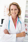 Ευτυχής μέσος θηλυκός γιατρός ηλικίας στη διαβούλευση του δωματίου στοκ φωτογραφίες