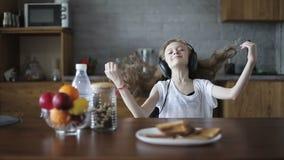 Ευτυχής μαθήτρια στα ακουστικά που χορεύουν στον πίνακα στην κουζίνα απόθεμα βίντεο