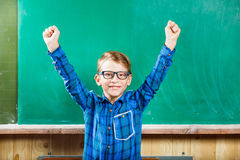 Ευτυχής μαθητής που αυξάνει τα χέρια ενάντια στον πίνακα κιμωλίας Στοκ Φωτογραφία