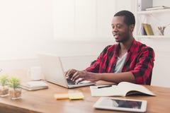 Ευτυχής μαύρος επιχειρηματίας στο περιστασιακό γραφείο, εργασία με το lap-top Στοκ φωτογραφία με δικαίωμα ελεύθερης χρήσης