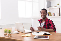 Ευτυχής μαύρος επιχειρηματίας στο περιστασιακό γραφείο, εργασία με το lap-top και έγγραφα Στοκ φωτογραφίες με δικαίωμα ελεύθερης χρήσης