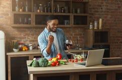 Ευτυχής μαύρος που εξετάζει το lap-top και το μαγειρεύοντας γεύμα Στοκ Φωτογραφίες