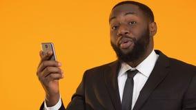 Ευτυχής μαύρος στο smartphone και την παρουσίαση εκμετάλλευσης κοστουμιών αντίχειρων, μετρητά πίσω app απόθεμα βίντεο