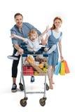 Ευτυχής μεταφορά γονέων χαριτωμένη λίγη συνεδρίαση γιων στο καροτσάκι αγορών Στοκ Εικόνες
