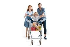 Ευτυχής μεταφορά γονέων χαριτωμένη λίγη συνεδρίαση γιων στο καροτσάκι αγορών Στοκ Εικόνα