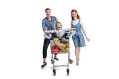 Ευτυχής μεταφορά γονέων χαριτωμένη λίγη συνεδρίαση γιων στο καροτσάκι αγορών Στοκ φωτογραφία με δικαίωμα ελεύθερης χρήσης