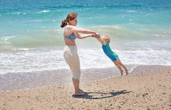 Ευτυχής μητέρα και λίγος γιος μωρών που έχουν τη διασκέδαση στις διακοπές παραλιών Στοκ Εικόνες