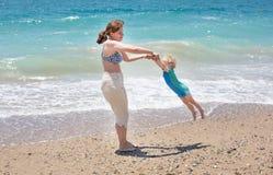 Ευτυχής μητέρα και λίγος γιος μωρών που έχουν τη διασκέδαση στις διακοπές παραλιών Στοκ Φωτογραφία