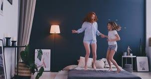 Ευτυχής μητέρα και η κόρη της που πηδούν στο κρεβάτι στο δωμάτιο παιδιών απόθεμα βίντεο