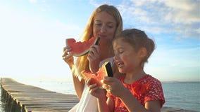 Ευτυχής μητέρα και η συνεδρίαση κορών της σε μια ξύλινη αποβάθρα και κατανάλωση ενός juicy καρπουζιού απόθεμα βίντεο