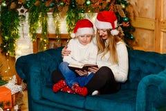 Ευτυχής μητέρα και λίγος γιος στο ταίριασμα των πουλόβερ και των κόκκινων καλυμμάτων που διαβάζουν μια συνεδρίαση βιβλίων στον κα στοκ φωτογραφία με δικαίωμα ελεύθερης χρήσης