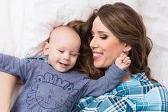 Ευτυχής μητέρα και ο γιος μωρών της που βρίσκονται σε ένα κρεβάτι από κοινού οικογένεια ευτυχής μητέρα παιδιών νεογέννητη Στοκ Φωτογραφία