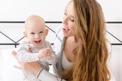Ευτυχής μητέρα και ο γιος μωρών της που παίζουν σε ένα κρεβάτι από κοινού οικογένεια ευτυχής μητέρα παιδιών νεογέννητη Στοκ Εικόνες