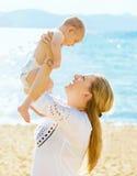 Ευτυχής μητέρα και ο γιος μωρών της στην παραλία Στοκ φωτογραφία με δικαίωμα ελεύθερης χρήσης