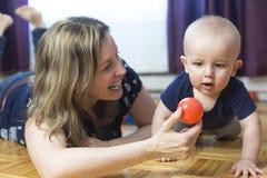 Ευτυχής μητέρα και ο 1χρονος γιος της που παίζουν με τη μικρή σφαίρα στο σπίτι Στοκ Φωτογραφίες