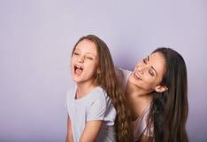 Ευτυχής μητέρα και συγκινημένο joying κορίτσι παιδιών που αγκαλιάζουν με τα συναισθηματικά πρόσωπα χαμόγελου στο πορφυρό υπόβαθρο στοκ εικόνες