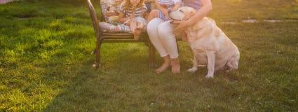 Ευτυχής μητέρα και δύο παιδιά με το χρυσό Retriever σκυλί στον κήπο, κινηματογράφηση σε πρώτο πλάνο στοκ εικόνα με δικαίωμα ελεύθερης χρήσης
