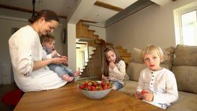Ευτυχής μητέρα με δύο γιους και κόρη που τρώνε τις ώριμες κόκκινες φράουλες απόθεμα βίντεο