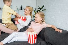 ευτυχής μητέρα με τα χαριτωμένα παιδάκια που τρώνε popcorn από κοινού στοκ φωτογραφία με δικαίωμα ελεύθερης χρήσης