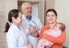 Ευτυχής μητέρα με τους ώριμους γιατρούς μωρών Στοκ Εικόνες