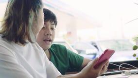 Ευτυχής μητέρα με το γιο στο εστιατόριο που μιλά και που παίζει στη ηλεκτρονική συσκευή τους απόθεμα βίντεο