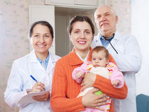 Ευτυχής μητέρα με το μωρό και τους γιατρούς Στοκ φωτογραφία με δικαίωμα ελεύθερης χρήσης