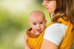 Ευτυχής μητέρα με το μωρό της σε μια σφεντόνα - σε πράσινο Στοκ Εικόνες