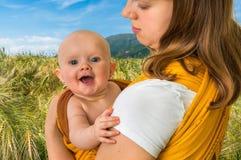 Ευτυχής μητέρα με το μωρό της σε μια σφεντόνα Στοκ εικόνα με δικαίωμα ελεύθερης χρήσης