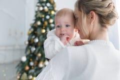 Ευτυχής μητέρα με το νέο γιο της στη Παραμονή Χριστουγέννων κοντά στο χριστουγεννιάτικο δέντρο στοκ εικόνες