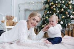 Ευτυχής μητέρα με το νέο γιο της στη Παραμονή Χριστουγέννων κοντά στο χριστουγεννιάτικο δέντρο στοκ εικόνες με δικαίωμα ελεύθερης χρήσης