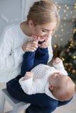 Ευτυχής μητέρα με το νέο γιο της στη Παραμονή Χριστουγέννων κοντά στο χριστουγεννιάτικο δέντρο στοκ εικόνα
