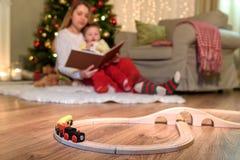 Ευτυχής μητέρα με το παιχνίδι γιων τους με τον πρότυπο σιδηρόδρομο στοκ εικόνες