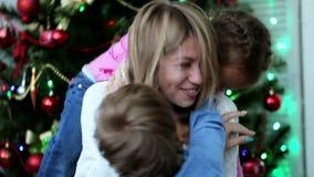 Ευτυχής μητέρα που έχει τη διασκέδαση με τα παιδιά της στο χρόνο Χριστουγέννων δίπλα στο χριστουγεννιάτικο δέντρο απόθεμα βίντεο