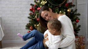 Ευτυχής μητέρα που έχει τη διασκέδαση με την κόρη παιδιών της δίπλα στο χριστουγεννιάτικο δέντρο απόθεμα βίντεο
