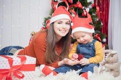 Ευτυχής μητέρα που δίνει στο δώρο Χριστουγέννων μωρών Στοκ Φωτογραφία