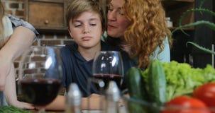Ευτυχής μητέρα που αγκαλιάζει το γιο μαγειρεύοντας στην κουζίνα, χαριτωμένη οικογένεια που επικοινωνεί προετοιμάζοντας τα τρόφιμα απόθεμα βίντεο