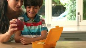 ευτυχής μητέρα που βάζει το μήλο στο καλαθάκι με φαγητό γιων της απόθεμα βίντεο