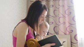 Ευτυχής μητέρα που διαβάζει ένα βιβλίο στο αγόρι παιδιών στο εσωτερικό Γλυκιά στιγμή με το βιβλίο ανάγνωσης μητέρων στο μωρό φιλμ μικρού μήκους