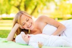 Ευτυχής μητέρα που εναπόκειται σε λίγο μωρό στο κάλυμμα Στοκ φωτογραφία με δικαίωμα ελεύθερης χρήσης