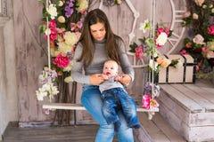 Ευτυχής μητέρα που κρατά το λατρευτό αγοράκι παιδιών Στοκ Εικόνες